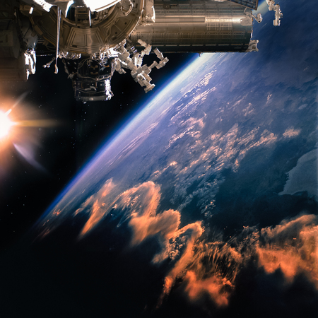 Spaceship on the orbit. Earth with clouds sunshine on the background. Stock Photo