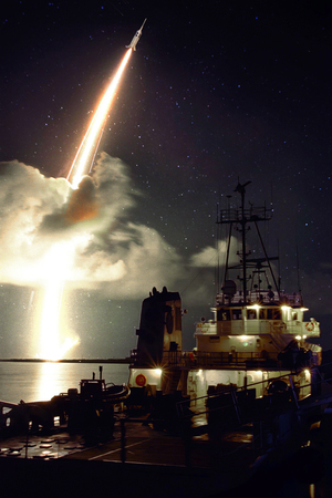 Missile launch at night above the sea, view from the ship.