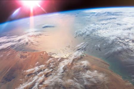The Suns glint radiates off the Atlantic Ocean above the African Mauritania.