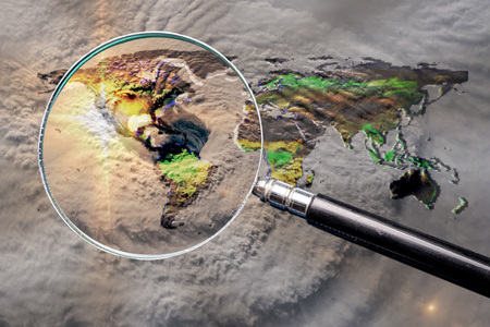 Collage with magnifying glass searching at the earth map with huge hurricane, and hurricane eye above the America.