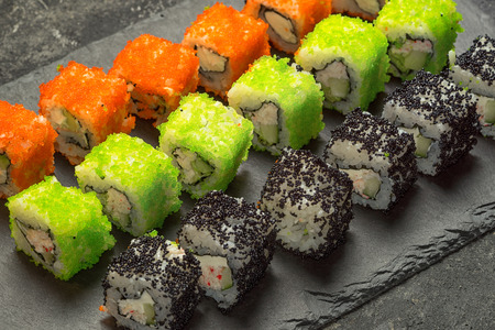 Set of assorted japanese sushi food on a black stone plate, close up angle view. Rolls with tuna, salmon, shrimp, crab and avocado. Sushi menu. 写真素材