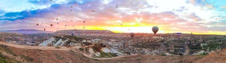 Panoramic view of the Hot Air balloons flying tour over Mountains landscape spring sunrice Cappadocia, Goreme Open Air Museum National Park, Turkey nature background.