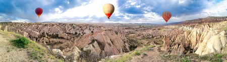 Panoramic view of the Hot Air balloons flying tour over Mountains landscape Cappadocia, Turkey nature background.