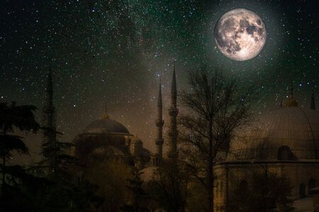 Sultan Ahmed Mosque at night, with starry sky and full moon.