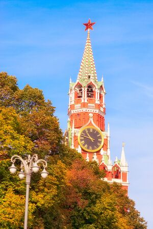 The Spasskaya Tower, or Saviour Tower, is the main tower on the eastern wall of the Moscow Kremlin which overlooks the Red Square. View from the autumnal trees. Stok Fotoğraf