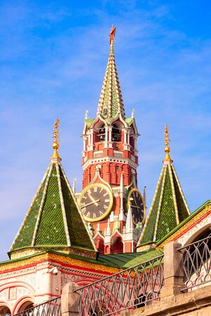 Unusual perspective on the Spasskaya Tower through the domes of St. Basil's Cathedral, Moscow, Russia. Sunny day.