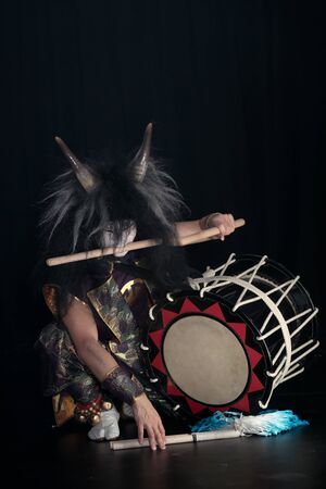 Taiko drummer in a wig and a demon mask on stage sitting holding drumstick on the mouth and drum on a black background.