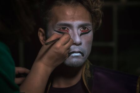 japanese taiko artist man puts makeup on face in the form of a demon mask, close up portrait