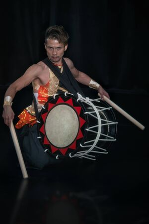 Taiko drummer with drum and drumsticks on the knee on stage on a black background