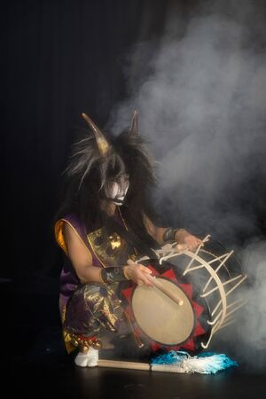 Taiko drummer in a wig and a demon mask on stage sitting with drumstick and drum on a black background with smoke in a stage light rays. Stok Fotoğraf