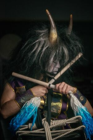 close up profile portrait of a demon with horns and wig with drumstick. japanese taiko drummer.