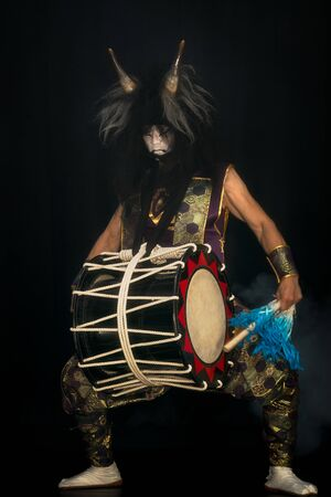 portrait of a demon with horns and wig with drum and drumstick on a stage. japanese taiko drummer.