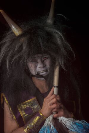 Smiling demon close up portrait. Taiko drummer in a wig and a demon mask sitting and smiling on black background.