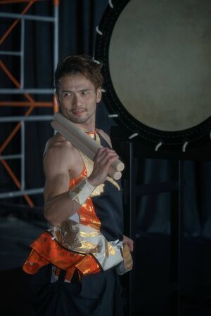 Taiko drummer with the big drum on stage on a black background. 写真素材