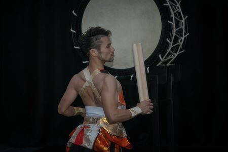 Taiko drummer hits the big drum on stage on a black background, back view.