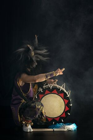 Demon from Japanese mythology. Full lenght portrait of an artist drummer Taiko in a wig with horns and make-up sits on stage and shakes head against a dark background.