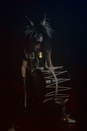 Demon from japanese mythology full lenght portrait in a darkness. Taiko drummer in a wig and a demon mask sitting and smiling on black background. 写真素材 - 132106346