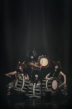 Four demons from Japanese mythology. Full lenght portrait of artists drummers Taiko in a wig with horns and make-up on stage against a dark background. Imagens