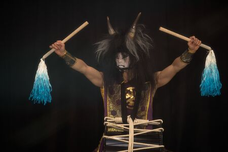 Demon from Japanese mythology. Portrait of an artist drummer Taiko in a wig with horns and demonic make-up drum on stage with his hands widly up with fringed drumsticks against a dark background. 版權商用圖片