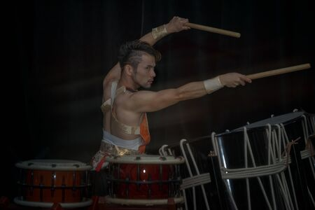 Taiko drummer drum drums with drumsticks in outstretched arms on stage on a black background 写真素材 - 132086724