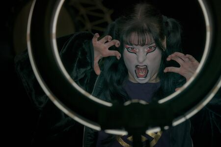 Girl with a halloween mask make-up makes a face inside a round frame of light. Halloween pirtrait. Banco de Imagens