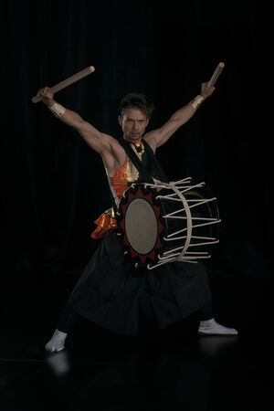 Taiko drummer with drum and drumsticks on stage on a black background