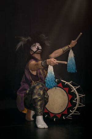 Taiko drummer in a wig and a demon mask on stage squarts with drumstick in his arms outstretched and taiko drum on a black background. Demon from Japanese mythology.