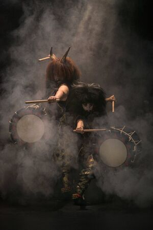 Two taiko drummers in a wig and a demon mask on stage with drumsticks and drums on a black background with smoke in light rays. Demons from Japanese mythology.