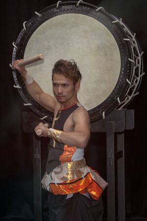 Portrait of a Japanese drummer Taiko with drumsticks on the background of a large drum.