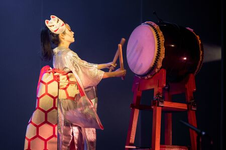 Traditional Japanese performance. Actress in white traditional japanese stage costume komono snd fox mask hits the drum.