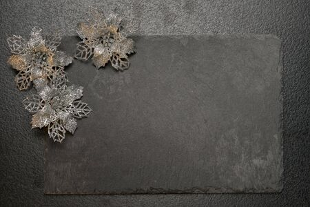black stone board with christmas decorative flowers on black textured cement background, top view vith copy space for your text
