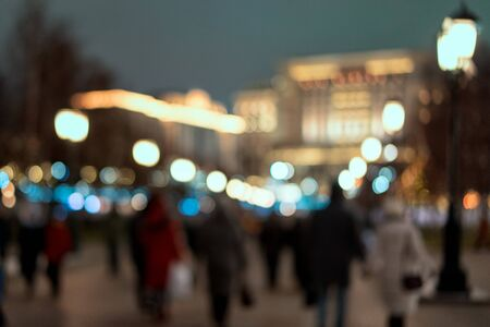 abstract blurred background of people walking in illuminated city at the evening