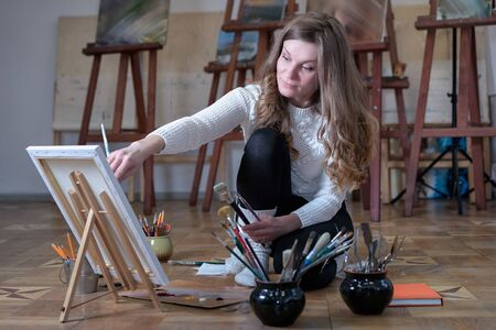 Woman artist paints while sitting on the floor in the art studio. Фото со стока