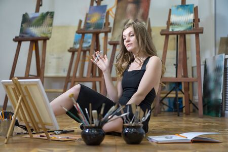 Portrait of a woman artist sitting on the floor and painting in the art studio.