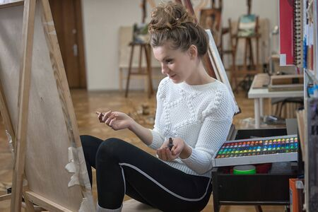 Portrait of a woman artist crayon painting in the art studio.