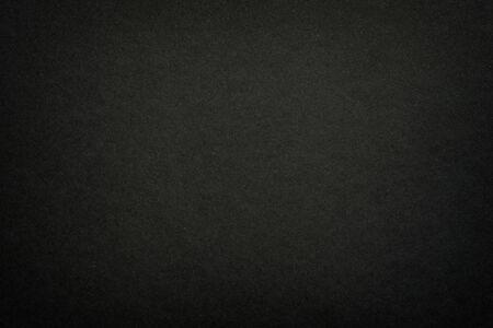 Schwarzer Mattpapierbeschaffenheitshintergrund. Oberfläche der abstrakten dunklen Textur. Graue leere Seite Hintergrund flach Nahaufnahme.