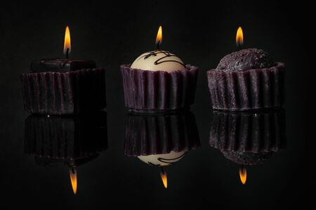 Three birthday chocolate cake muffins candles on a black mirror surface with reflections on black background.