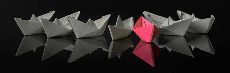 Origami paper ship with sailboats, leadership, marketing concept, social media influencers, HR recruiter, disruptive innovation, standing out of the crowd concept. Stock Photo