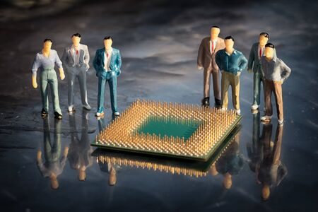 Group of miniature model of businessmen standing around the cpu in a reflective surface. Microelectronic engineering concept.