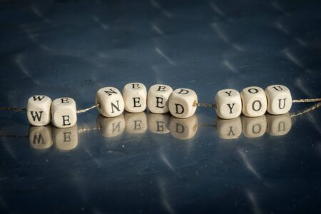 Wooden cubes with we need you inscription strung on a thread on reflective table. The recruitment business concept.