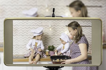 Young female blogger with two daughters, live streaming a cooking, baking cookies with children show on social media using a smartphone.