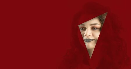 the face of a young beautiful girl with a bright make-up and with plump dark lips peeks into a hole in red paper. Fashion, beauty, make-up, cosmetics, beauty salon, style, personal care, geometry.