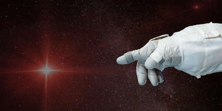 Astronaut hand pointing toward the star with background of deep space. Stockfoto