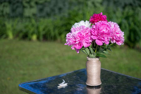 Bouquet of pink and white peonies flowers in a vase on a table in the summer outdoors. Stockfoto