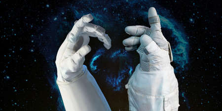 Bright stars in a night sky arranged in the shape of a heart, heart galaxy in astronaut hands. Love shape astronaut hands. Elements of this image furnished by . Stock Photo