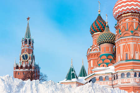 Snow pile near St. Basil's Cathedral and Spasskaya tower, winter in Moscow, Russia.