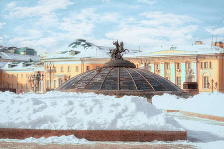 Snow pile at Manege Square. Glass cupola crowned by a statue of Saint George, holy patron of Moscow. (Inscription in Russian: names of famous cities in the world). Winter in Moscow, Russia.