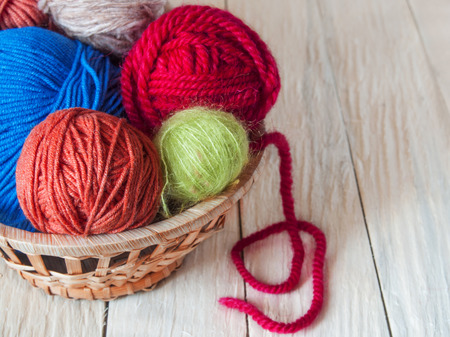 Yarn for hand knitting in different colors, needles, hooks lie on a wooden table
