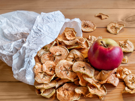Dried apples poured from a paper bag on the table top is a fresh red ripe juicy apple