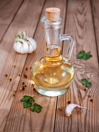 A glass decanter with vegetable oil on a wooden background surrounded by greenery, garlic and pepper is closed with a cork